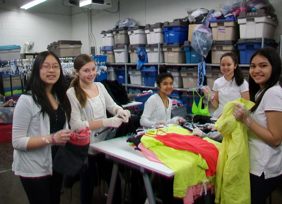 Volunteers from Holy Cross School sort clothing